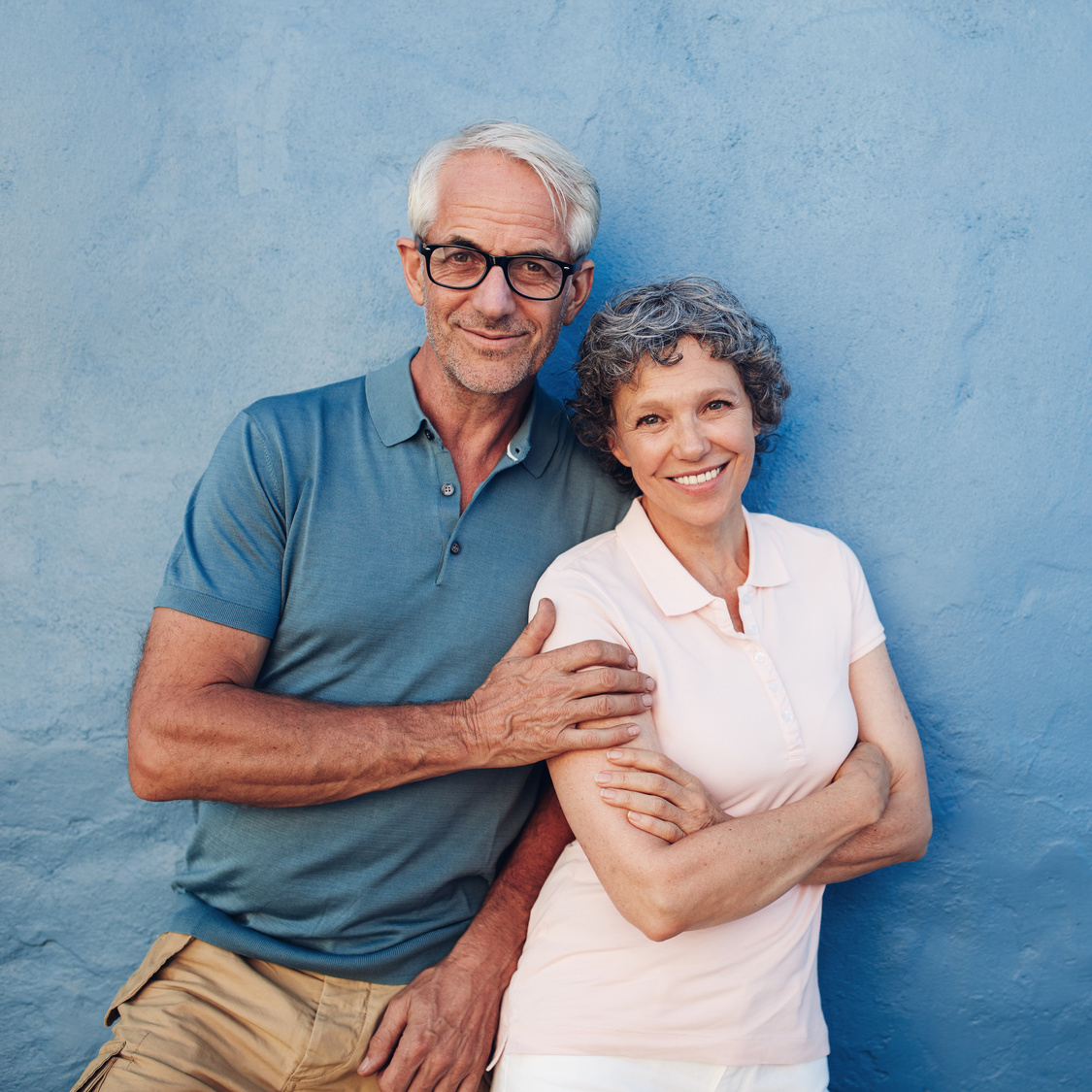 Portrait of happy mature couple standing together against blue wall. Middle aged man and woman looking at camera and smiling on blue background